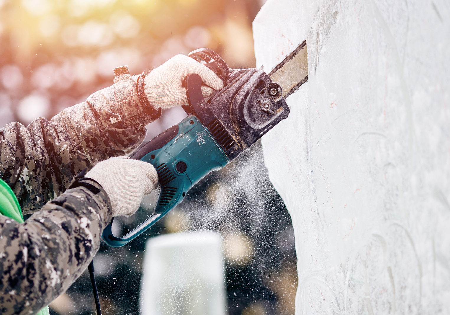 Ice sculpture carving man use chainsaw cut frozen winter