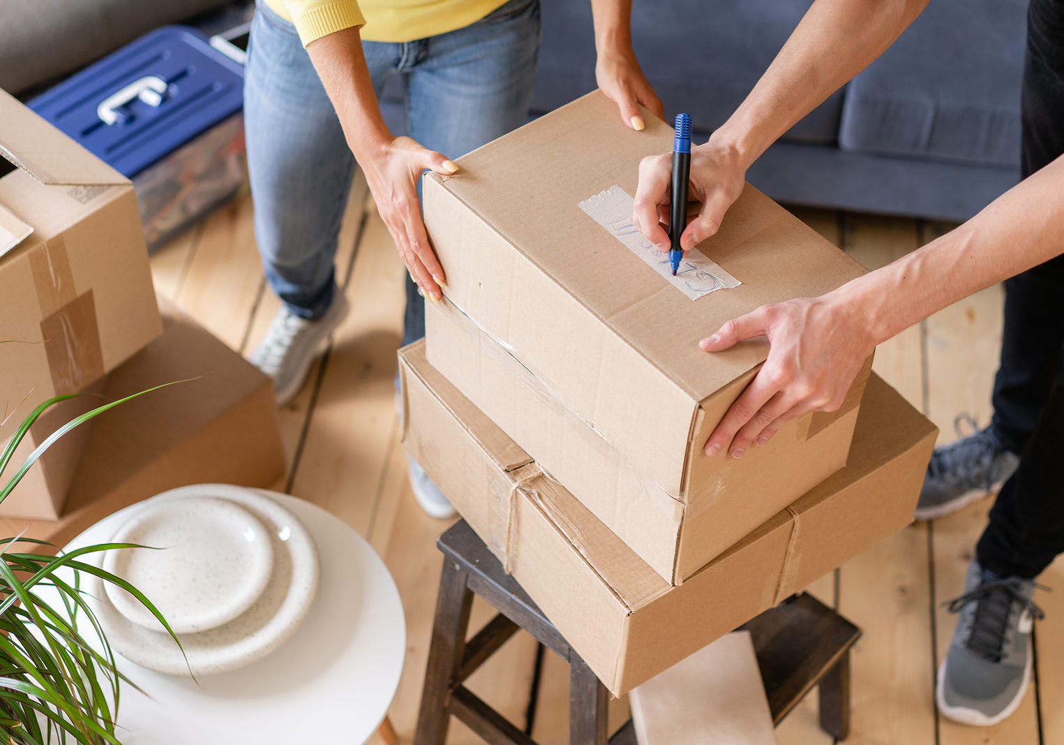 Close up of hand packing cardboard box, concept moving house. Young couple moving to a new apartment together. Relocation concept