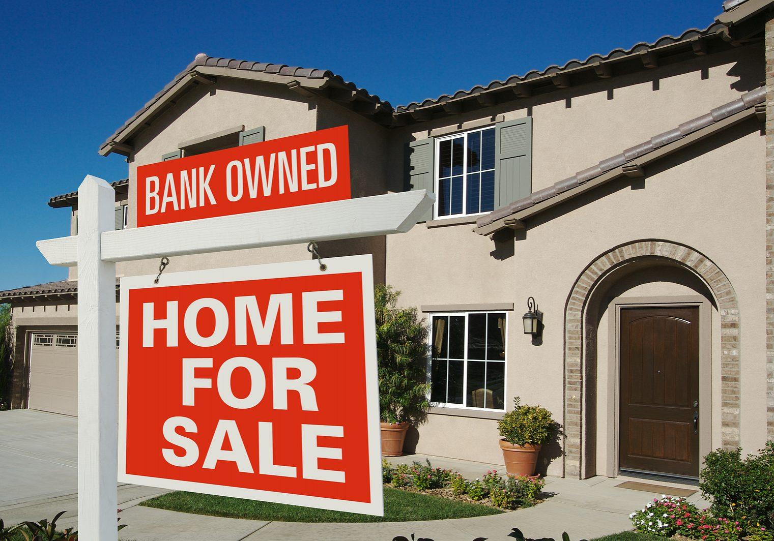 Bank Owned Home For Sale Sign in Front of New House on Deep Blue Sky